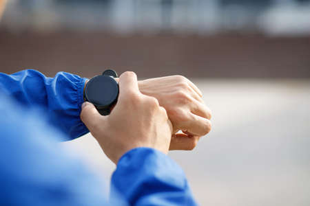 Running athlete man looking at smartwatch heart rate monitor GPS smart watch.