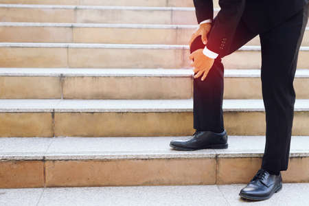 The businessman is walking up the stairs, he has a lot of knee pain.