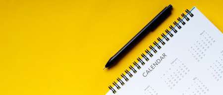 White clean calendar and pen on yellow background with copy space Stock fotó