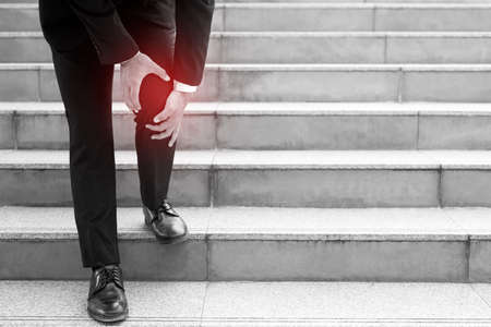 A businessman walking down the stairs, his knee ached. Foto de archivo