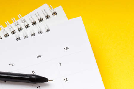 White clean calendar on solid yellow background with copy space, business meeting schedule Foto de archivo