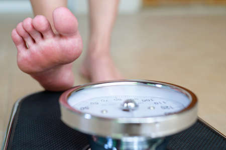Female feet standing on electronic scales for weight control on wooden background. The concept of slimming and weight loss Foto de archivo