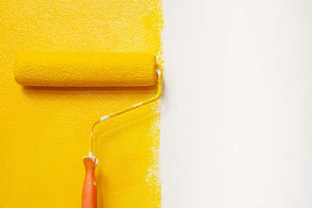 Roller Brush Painting, Worker painting on surface wall Painting apartment, renovating with yellow color paint.