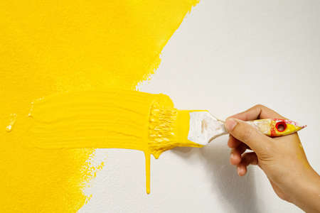 The painter is painting the walls in yellow with the interior of the home living room.