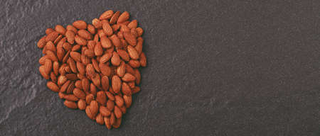 Heart shaped almond on gray background Foto de archivo