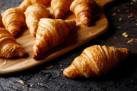 freshly baked croissants on wooden cutting board