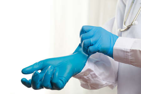 Doctor wearing blue rubber gloves to protect against COVID-19 at the hospital
