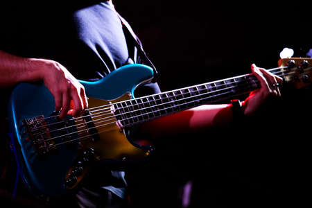 Musician holding bass guitar performing a concert at night pub