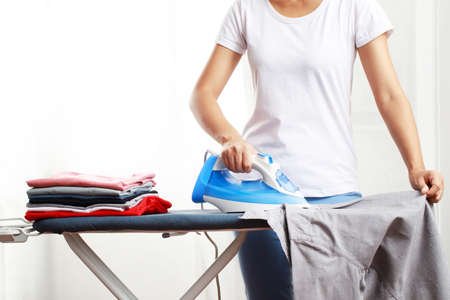woman is ironing a shirt at home