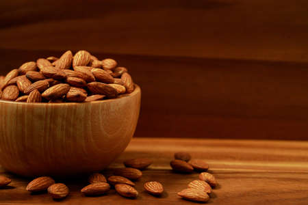 Almond in wooden bowl in the kitchen Imagens