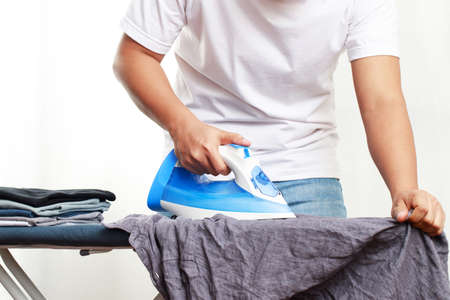 A man is ironing a shirt at the laundromat Imagens