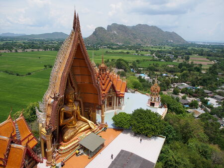 Golden buddha statue with rice fields and mountain, Wat Tham Sua (Wat Tham Khao Noi), Tha Moung, Kanchanburi, Thailand photo