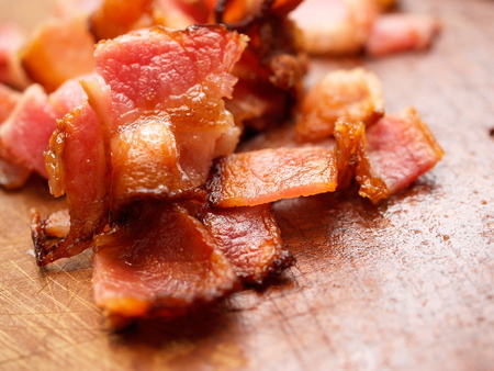 Cooked bacon pieces on wood.