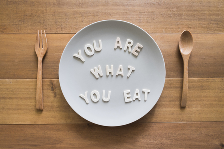 """health care concept.quote """"you are what you eat"""" on plate with spoon and fork"""