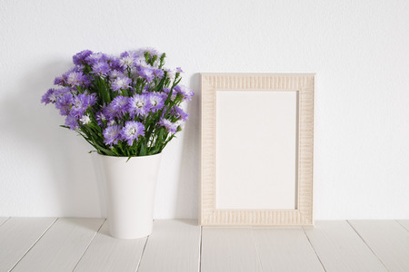 white wood floor: white frame with violet flower on table. Stock Photo