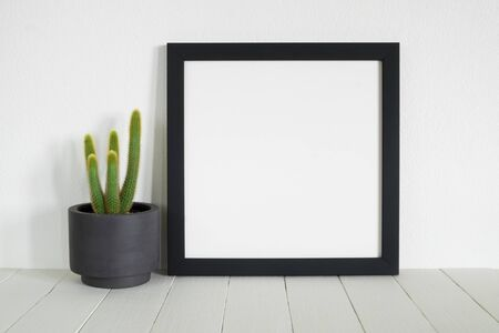 white wood floor: blank frame photo with cactus pot on table.minimal style home decoration