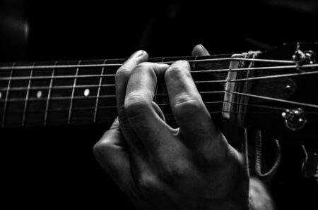 bn: Detalle de un artista tocando la guitarra