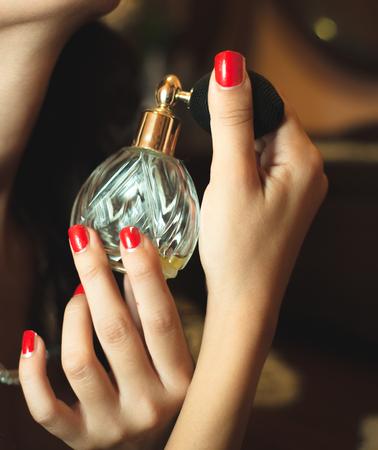 Woman puts perfume on neck
