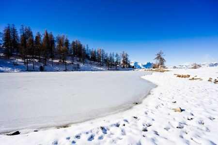 Frozen lake under a blue sky in Sauze DOulx Valle Susa