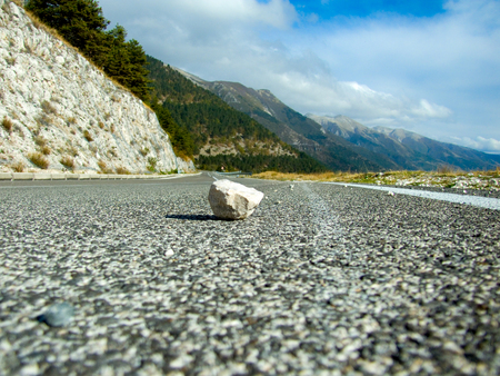 Falling stone on the road on mountain landscape