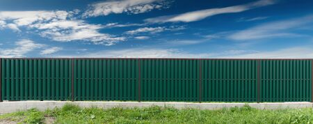 Green metal fence. Blue sky with clouds. Front view.