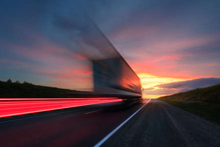 Blurring. A large truck is driving along the highway at high speed. Sky with bright red clouds. Delivery of cargo. Archivio Fotografico