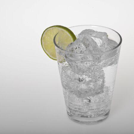 wasser: Klares, kaltes Getränk mit Eiswuerfeln und Limette