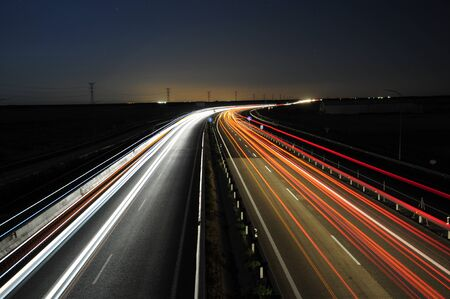 trails of lights of cars passing by highway at night