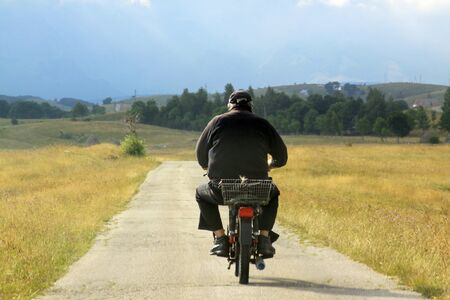 Local man on moped on Durmitor mountains ring road, Montenegro in summer