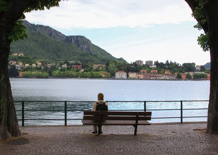 LECCO, ITALY - May 24, 2013: Tourist resting on bench looking at the lake