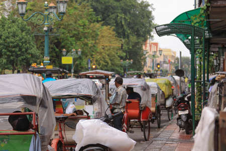 Rickshaws waiting in line on Malioboro street jalan in Yogyakarta, Yogya, Java, Indonesia. Becak taxi with one horse drivers waiting for tourists to take on tour around the city. Editorial