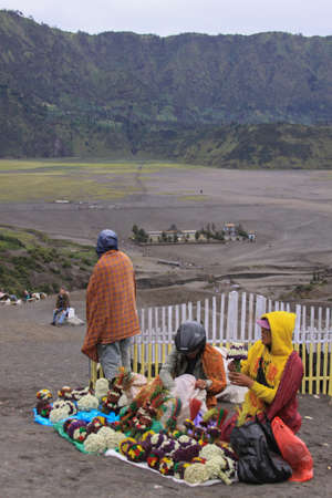 Bromo, Indonesia - June 14, 2013: Indonesian locals selling flowers to tourists on Mount Bromo, Java Indonesia. Bromo Tengger Semeru National Park. Editorial