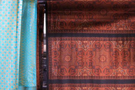 Batik textile with wax hanging in Winotosastro factory in Yogyakarta, Java, Indonesia. Batik motif sample designs on cloth. The textile peace is hanging to dry in Winotosastro batik factory