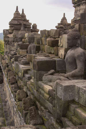 Buddha statues on building side walls at Borobudur buddhist temple, Java, Indonesia. Candi Borobudur, the largest Buddhist temple. Exotic landmark with mountains and clouds at sunset. Editorial