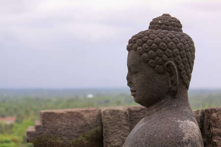 Side portrait of buddha statue in stupa at Borobudur buddhist temple landscape, Java, Indonesia. Candi Borobudur, the largest Buddhist temple. Exotic landmark with mountains and clouds at sunset. Editorial