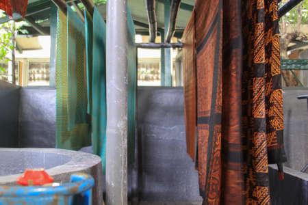 Batik hanging in Winotosastro factory in Yogyakarta, Java, Indonesia. Batik motif sample designs on cloth. It depicts floral design symbols. The textile piece is hanging to dry in batik factory Editorial