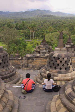 BOROBUDUR, INDONESIA - June 10, 2013: Couple meditate at Borobudur temple, Java, Indonesia. Candi Borobudur is the largest Buddhist temple and one of the most important tourist attraction in Indonesia 에디토리얼