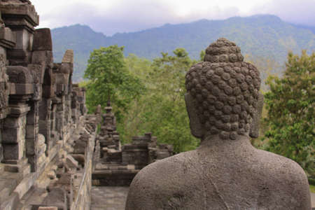 Behind the back of single buddha statue in meditation at Borobudur buddhist temple, Java, Indonesia. Candi Borobudur, the largest Buddhist temple. Exotic landmark with mountains and clouds at sunset.