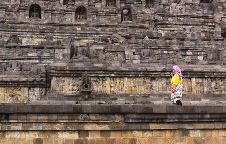 BOROBUDUR, INDONESIA - June 10, 2013: Local muslim woman at Borobudur temple, in Java Indonesia, along stone wall with Buddha statues