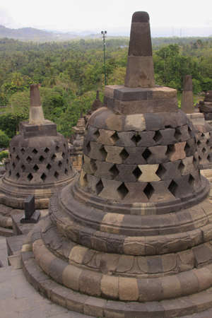 One stupa in foreground and stupas in background on top of Candi Borobudur, the largest Buddhist temple in the world. Mountains and clouds at sunset, in distant landscape background.