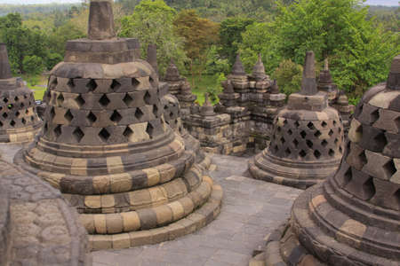 Stupas arrangement on stairs at Borobudur buddhist temple. Candi Borobudur is the largest Buddhist temple in the world. Mountains and clouds at sunset, in distant landscape background.