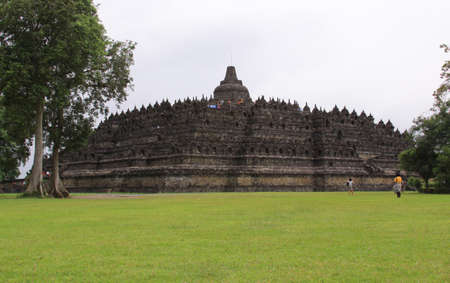 BOROBUDUR, INDONESIA - June 10, 2013: Visitors at Borobudur temple. Landscape full view from temple base. Candi Borobudur is the largest Buddhist temple in the world.
