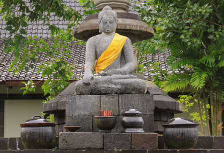 Sitting Buddha stone statue decorated with yellow scarf in Indonesia, with offerings in pots