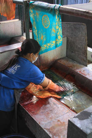 Worker washes dyed Batik to dry in Winotosastro factory in Yogyakarta, Java, Indonesia. Batik motif sample designs on cloth. Hand drawing the white fabric with batik motif using Canting tool.