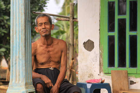 Probolinggo, Indonesia - June 14, 2013: Old Indonesian man on porch of his house in a village in Java. Walking in the countryside of an Indonesian village in East Java