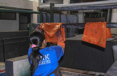 Worker hang wet Batik to dry in Winotosastro factory in Yogyakarta, Java, Indonesia. Batik motif sample designs on cloth. Hand drawing the white fabric with batik motif using Canting tool
