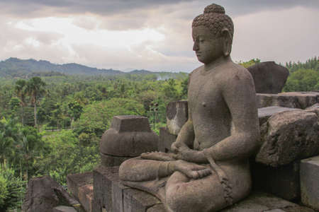 Front view of single buddha statue in meditation at Borobudur buddhist temple, Java, Indonesia. Candi Borobudur, the largest Buddhist temple. Exotic landmark with mountains and clouds at sunset. Editorial