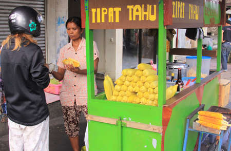 Tourist bargaining with steamed corn seller in the street, in Bali. Customer purchasing food from an indonesian street vendor. Street food vendors in Indonesia are almost everywhere.