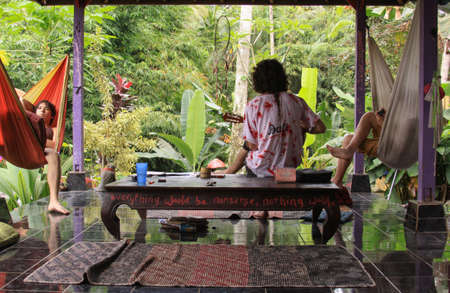 Guitarist plays relaxing tunes and two people listening in hammock under bale, In Ubud. Hippie relaxed atmosphere in home stay resort in Ubud, Bali, Indonesia. Lockdown singing activity Editorial
