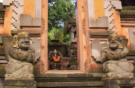 Door or gate to enter into traditional balinese garden architecture detail. Open style pavilion or local pavilion called bale in the garden. Travel photography with ethnic art. Ubud, Bali, Indonesia